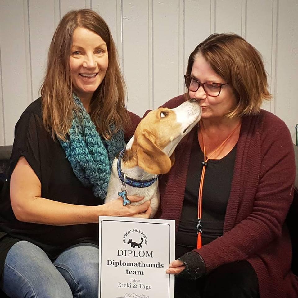 Hundpsykolog Kicki Fellstenius och diplomathunden Oskar tar emot diplom från Cilla Danielsson på Hundens Hus.