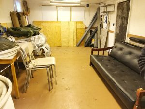 Inomhussöket med en soffa, några travar med stolar och lite annat bråte